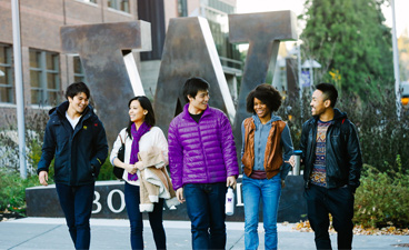 Image of a students walking outside UW Bothell in front of large bronze W