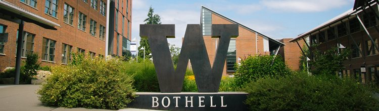 "Photo of the UW Bothell campus ""W"" metal sign which is positioned in between UW1 and UW2. It's a sunny day and there are plants growing around the W sign."
